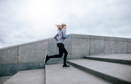 Side view full length shot of fit young woman running up stairs. Fitness female on morning workout. Stock Photo