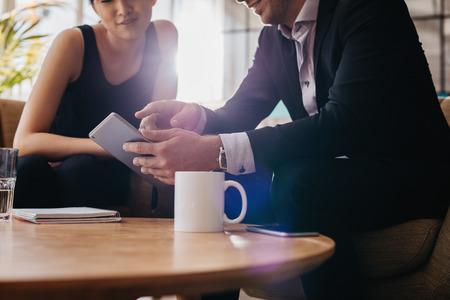 사업가 및 디지털 태블릿 사용하여 사무실 로비에서 모임 데 사업가 자른 된 총. 터치 스크린 컴퓨터를 사용하는 회사원입니다.