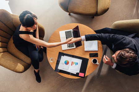 Bovenaanzicht van jonge business partners handen schudden op de deal op kantoor. Documenten en laptop op tafel met statistieken en grafieken. Stockfoto