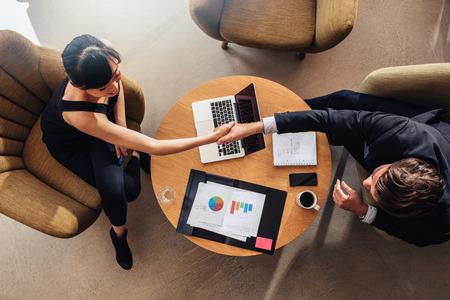 Draufsicht der jungen Geschäftspartner Hände auf Deal im Büro, schütteln. Dokumente und Laptop auf dem Tisch zeigt Statistiken und Grafiken. Standard-Bild - 67456902