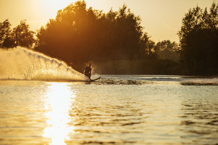 wakeboarding: Man water skiing on lake with splashes of water. Man wakeboarding at sunset. Stock Photo