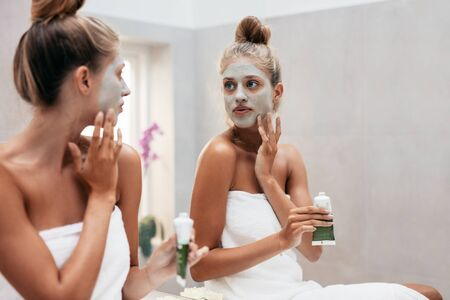 face mask: Young woman with cosmetic mask on face in bathroom. Female applying face mask infront of mirror. Stock Photo