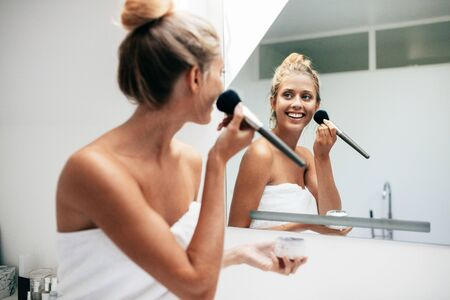 Beautiful young woman with brush applying makeup in bathroom. Female looking into the bathroom mirror and putting on makeup.