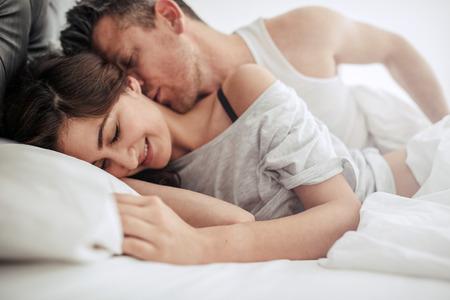 관능적 인 전희를 즐기고 침실에서 로맨틱 커플입니다. 미소하고 사랑하는 여자. 스톡 콘텐츠