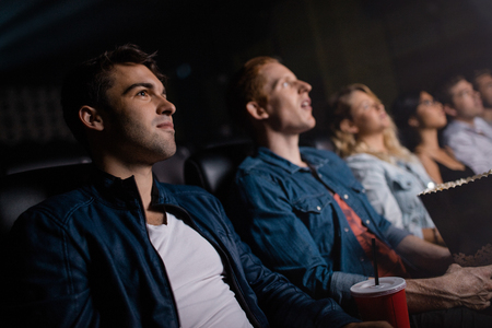 cinema people: Young man with friends watching movie in cinema. Group of people in multiplex theater.