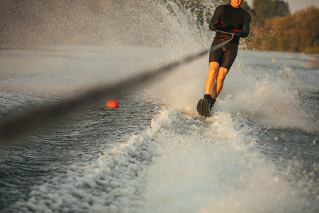 wakeboarding: Man riding wakeboard on wave of motorboat in a lake. Male water skiing behind a boat.