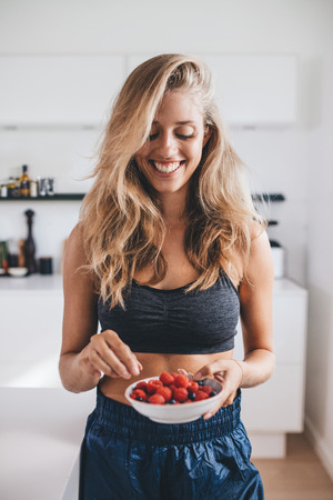 breakfast bowl: Healthy young woman in kitchen holding a bowl of berries. Smiling woman having healthy breakfast at home.