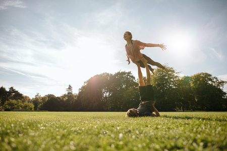 Fit young couple doing acrobatic yoga in park. Man lying on grass and balancing woman in his feet.