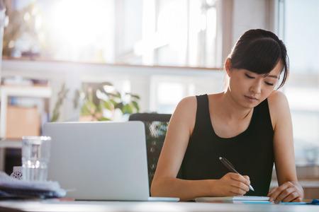 테이블 및 쓰기 노트에 앉아 젊은 여자가 샷. 그녀의 책상에서 작업하는 사업가.