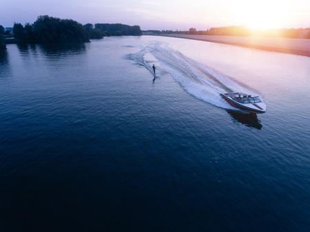 Vista aerea dell'uomo che wakeboarding sul lago al tramonto. Sci d'acqua sul lago dietro una barca.