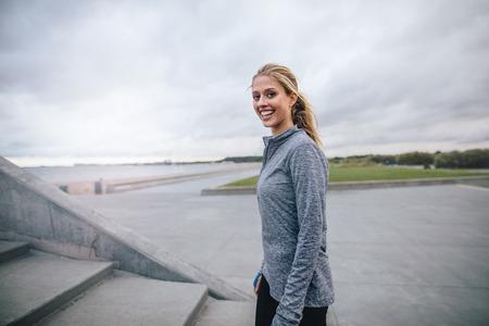 Ritratto di felice giovane donna in piedi all'aperto e sorridente. Fitness modello femminile all'aperto in mattinata.