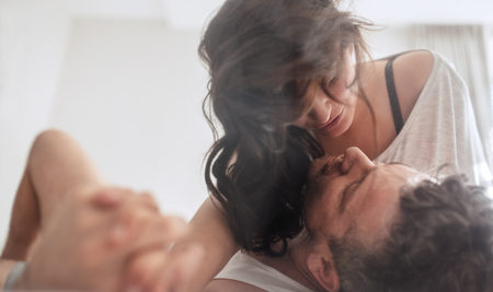 Intimate young couple in bedroom enjoying each other. Stock Photo
