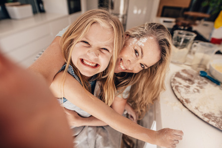 food technology: Smiling little girl and woman in kitchen taking selfie. Happy young mother and daughter cooking food. Stock Photo
