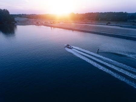 Aerial view of man water skiing on lake behind boat. Man wakeboarding at sunset.
