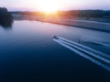 wakeboarding: Aerial view of man water skiing on lake behind boat. Man wakeboarding at sunset.