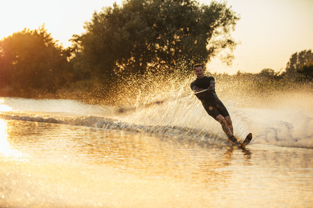 wakeboarding: Man wakeboarding on a lake with splashes of water. Wakeboarder surfing across the lake. Stock Photo