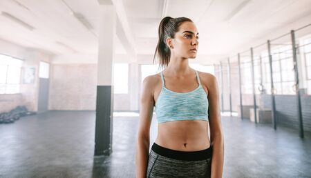 healthy looking: Portrait of healthy young woman standing in gym and looking away. Fitness woman in sportswear. Stock Photo