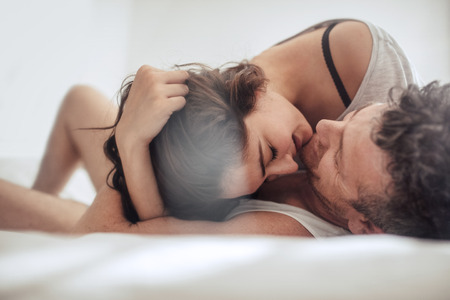 sexual foreplay: Young couple caressing in bed together. Romantic couple in a relationship enjoying on bed.