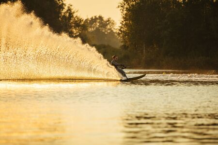 sportsperson: Man riding wakeboard on lake with splashes of water. Man water skiing at sunset.