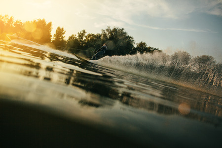 sportsperson: Low angle shot of man water skiing at sunset. Man riding wakeboard on lake with splashes of water. Stock Photo