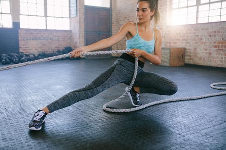運動ジムでロープで若い女性のショット。フィットネス女性ジムでロープを引っ張るします。