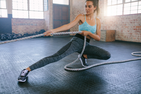 Shot of young woman exercising with rope at a gym. Fitness female pulling rope at gym. Stok Fotoğraf - 68310049