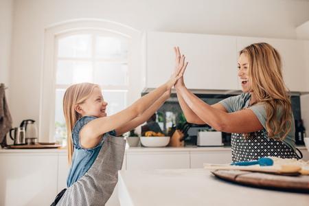Mała dziewczynka i jej matka w kuchni dając piątkę. Matka i córka w kuchni do gotowania. Zdjęcie Seryjne