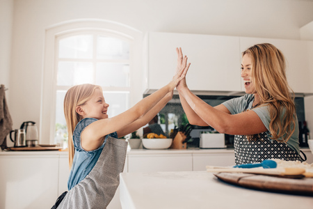 Niña y su madre en la cocina dando choca esos cinco. Madre e hija en la cocina de cocina. Foto de archivo