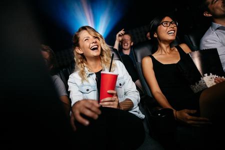 젊은 사람들이 영화관에서 영화를 보면서 웃고. 멀티 플렉스 시네마 음주 및 팝콘 친구의 그룹. 스톡 콘텐츠