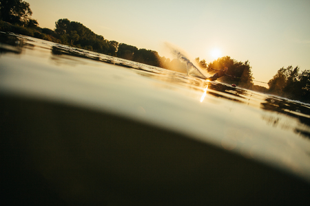 wakeboarding: Low angle shot of man wakeboarding on a lake. Water skiing at sunset. Stock Photo