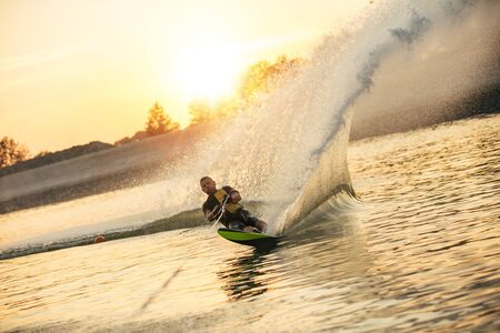 wakeboarding: Waterskier moving fast in splashes of water at sunset. Man wakeboarding on a lake