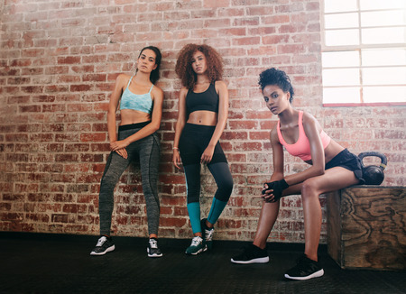 Portrait of young women resting after workout in gym. Mixed race group of female relaxing in gym after training.