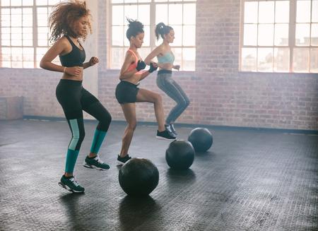 Junge Frauen in Aerobic-Kurs mit Medizinbällen auf dem Boden ausüben. Drei Frauen trainieren zusammen in der Turnhalle zu tun.