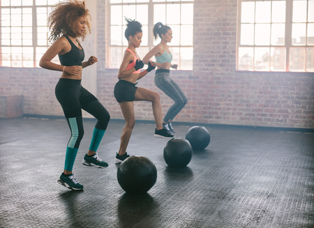 Young women exercising in aerobics class with medicine balls on floor. Three females doing workout together in gym. Archivio Fotografico