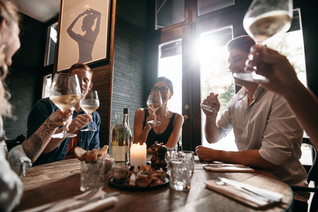 dinner party: Diverse group of young people having wine at restaurant. Men and women meeting at a restaurant for dinner. Stock Photo