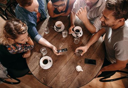 카페에서 친구의 그룹과 스마트 폰을 찾고. 옆에 앉아 자신의 친구에게 뭔가 게재하는 사람 (남자).