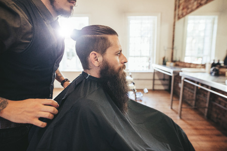 hair man: Side view shot of handsome bearded man in a black cutting hair cape in the barbershop, with hairdresser standing by. Man sitting at hair salon. Stock Photo