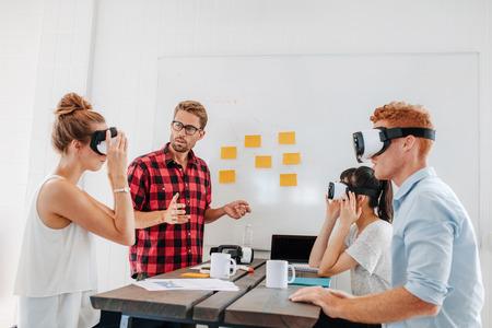 가상 현실 고글 테이블에 앉아 젊은 남성과 여성. 모임 사무실에서 가상 현실 헤드셋을 테스트하는 비즈니스 팀.