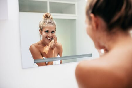 the caucasian beauty: Smiling young woman reflection in mirror applying face cream in bathroom. Caucasian female doing beauty treatment at home.