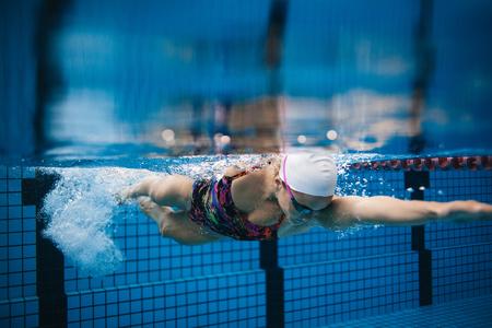 풀에서 수영하는 젊은 sportswoman의 수 중 쐈 어. 여성 수영 수영장 내부 행동입니다.