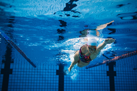 sportsperson: Underwater shot of woman training in swimming pool. Female swimmer in action inside swimming pool.