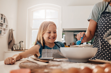 baking: Happy little girl standing in kitchen and her mother cooking food. Mother and happy daughter baking in kitchen.
