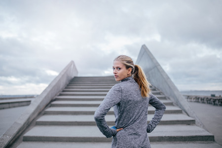 Outdoor shot of young woman standing by a stairs and looking over shoulder. Fitness female model ready for a run. Stock Photo - 69273914