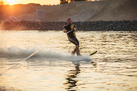 sportsperson: Outdoor shot of man wakeboarding on lake. Water skiing on lake behind a boat.