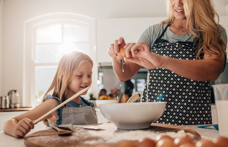 cracking: Mother cracking an egg into bowl with her daughter in kitchen. Woman and little girl preparing food in kitchen.