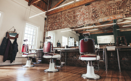 Horizontal shot of empty chairs in retro styled barbershop. Hair salon interior. Фото со стока