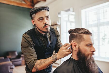 Hairdresser checking symmetry of haircut of his client at barbershop. Bearded man getting haircut by barber at barbershop