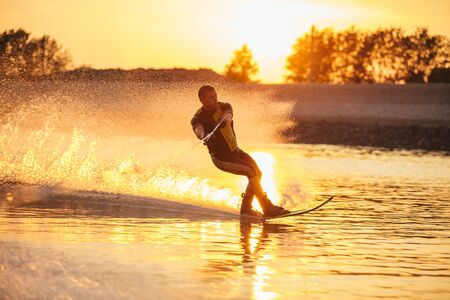 sportsperson: Outdoor shot of man water skiing at sunset . Man wakeboarding on a lake.