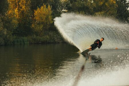 sportsperson: Wakeboarder skiing on lake with splash of water. Man practicing wakeboarding stunts.