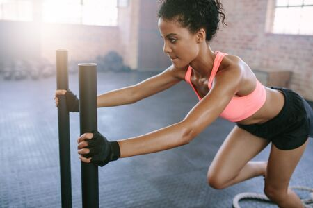 prowler: Side view shot of fit young woman pushing the sled at gym. African woman doing intense physical workout in gym. Stock Photo